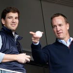 """FILE - In this May 4, 2014, file photo, Denver Broncos quarterback Peyton Manning, right, points out something in the stadium to his brother, New York Giants quarterback Eli Manning, from New York Yankees' Derek Jeter's suite during a baseball game between the Yankees and the Tampa Bay Rays at Yankee Stadium in New York. Peyton Manning had a little fun with little brother Eli's sad face at the Super Bowl during an appearance on NBC's """"Tonight Show.""""  (AP Photo/Kathy Willens, File)"""