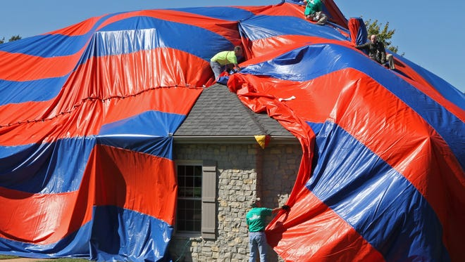 In this photo taken on Sunday, Oct. 5, 2014, workers from McCarthy Pest Control finish covering a house in Dardenne Prairie, Mo. with a tarp in preparation for fumigating the home to get rid of brown recluse spiders.