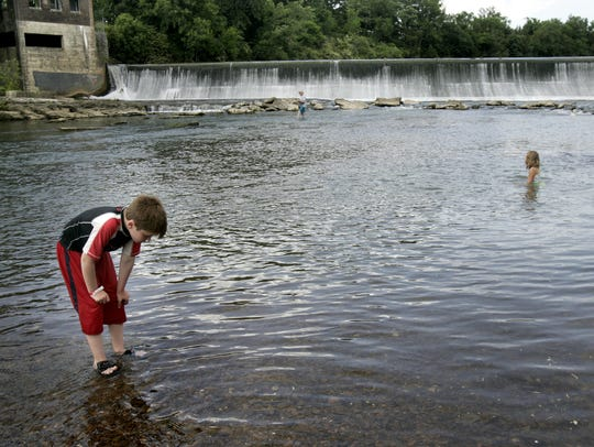 This file photo from May 29, 2013, shows Logan Daniels, 7, playing in Stones River at Walter Hill Dam, as Graclyn McCann, 8, plays in the water in the background.