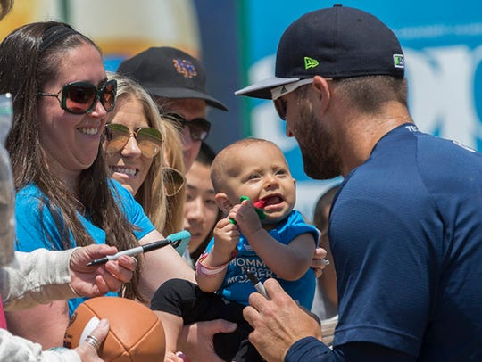 Tim Tebow takes a fans baby so they can be in a photo