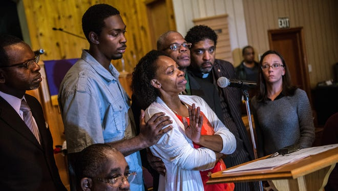 In this Dec. 1 2014 photo, Claudia Lacy, center, cries as she thanks the people who showed up at First Baptist Church in Bladenboro, N.C., to listen to the Rev. Dr. William Barber II, president of the North Carolina State Conference of the NAACP, talk about the developments in the investigation of her son's death. Lennon Lacy, a 17-year-old, was found hanging from a swing set in the middle of a trailer park in late August. Surrounding Claudia Lacy are attorney Alan Rogers, left; Wilson Lacy, sitting; Lennon' brother Pierre Lacy; Rev. Gregory D. Taylor; Rev. William Barber II; and attorney Heather Rattelade.