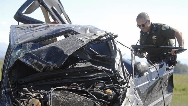 Montana Highway Trooper Michael Walrath inspects the wreckage of a Jeep Cheeroke involved in a crash on Interstate 90 between Belgrade and Manhattan in 2009.