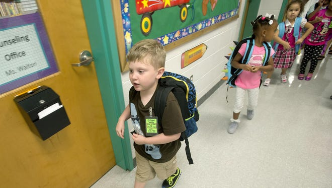 Gibson Webb, 5, walks with members of his class down the hallway to his mother's classroom at Emma Elementary School after his first day of kindergarten on Aug. 19.