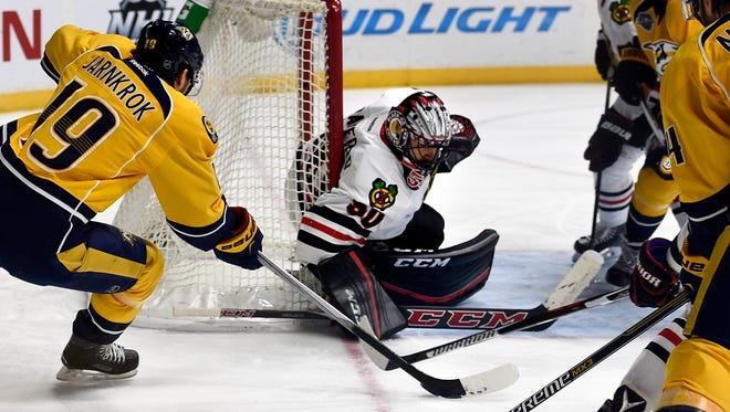 Predators center Calle Jarnkrok (19) has his shot blocked by Blackhawks goalie Corey Crawford (50)  in the third period Tuesday.