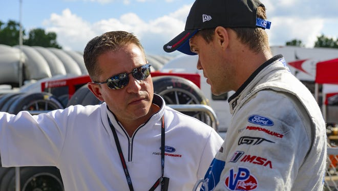 """Global director of Ford performance Dave Pericak, left, talks with Dirk Müller. Pericak is responsible for Ford-backed cars crossing the finish line first. """"I'm proud we race today for many of the same reasons Mr. Ford raced in 1901,"""" Pericak said."""