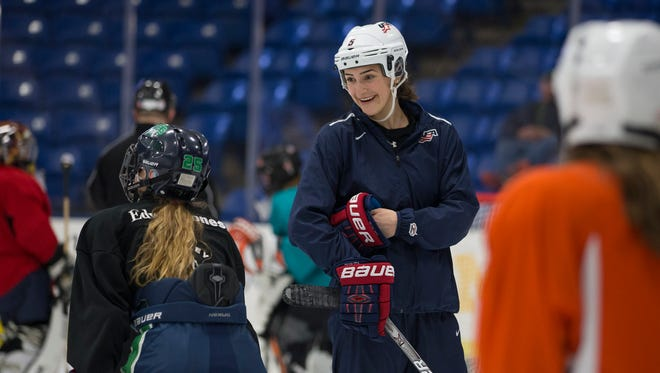 Megan Keller of Team USA's women's hockey team shares a smile with girls players during Tuesday's clinic.