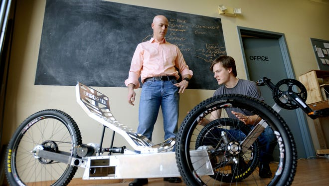 """Tom Ryan, left, the Kauffman Foundation entrepreneur in Residence, talks with Jesse Lee, co-founder of Outrider USA, about the parts on one of his ultra-light adventure vehicles at the shop in Fletcher on Thursday. Ryan described what he does as giving """"direct problem solving in a hands-on way,"""" instead of just business feedback."""