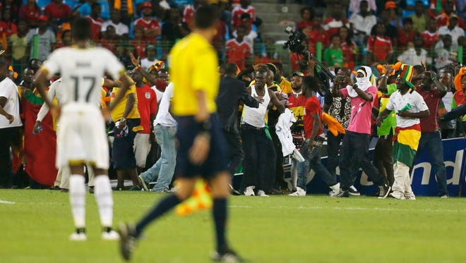 Security and CAF officials try to protect Ghana fans after Equatorial Guinea fans threw objects during their African Nations Cup semi-final soccer match.