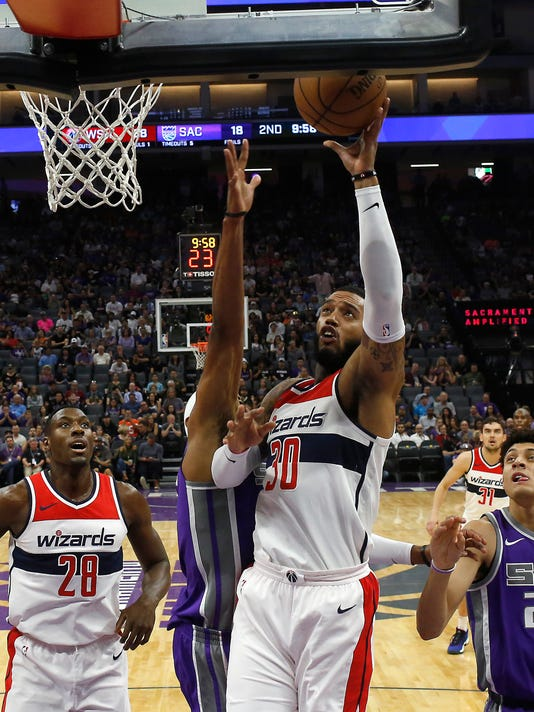 Sacramento Kings guard Vince Carter, second from left, tries to block the shot of Washington Wizards forward Mike Scott, third from left, during the first half of an NBA basketball game, Sunday, Oct. 29, 2017, in Sacramento, Calif. (AP Photo/Rich Pedroncelli)