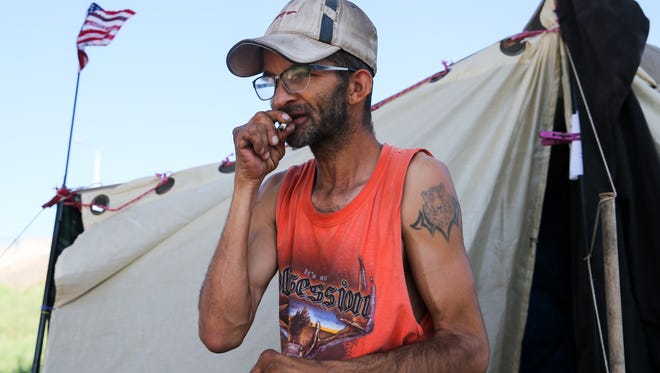 Reggie Felton lights a cigarette in the tent city under the Houston Harte Expressway in San Angelo. Felton is an unofficial leader of the camp, which he started with a couple who moved to Arkansas to find work.