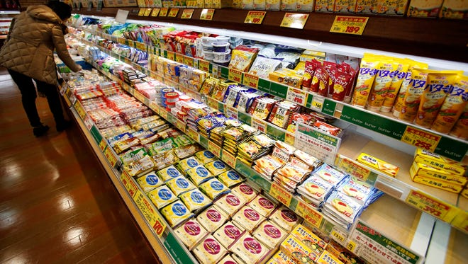 A shopper chooses dairy products as the shelf selling butter, right, is almost empty at a supermarket in Tokyo on Dec. 9.