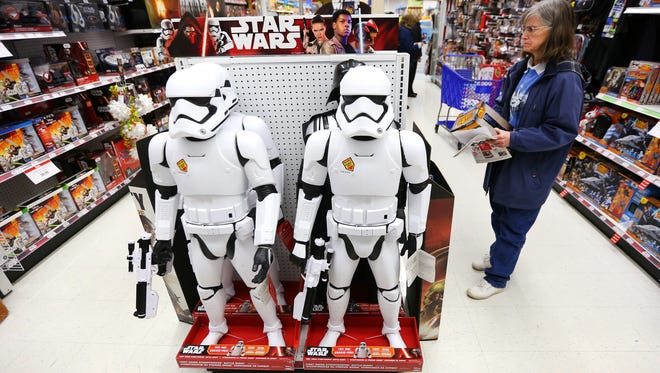 "Karen Simonton looks at ""Star Wars"" toys for her great-nephews while shopping Friday, Nov. 27, 2015, at Toys R Us in Salem, Ore."