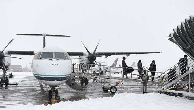 Passengers unload off a recently arrived plane at the Reno-Tahoe International Airport during a snowy Christmas Eve day in Reno on Dec. 24, 2015.