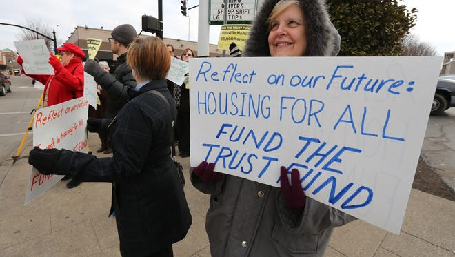 Trish Ramey, with the group CLOUT (Citizens of Louisville Organized and United Together), protest across the street from the groundbreaking.  They contend that the city should be funding the Affordable Housing Trust Fund rather than give incentives to the Omni.January 29, 2016