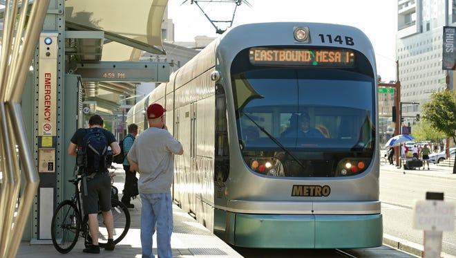 Commuters ride light rail along East Jefferson Street Wednesday, August 26, 2015 in Phoenix, Ariz.