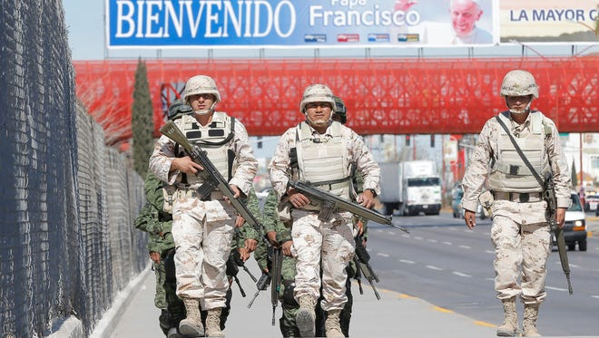 Mexican soldiers march around Parque Central in Juarez as they secure the area for the arrival of Pope Francis on Wednesday.