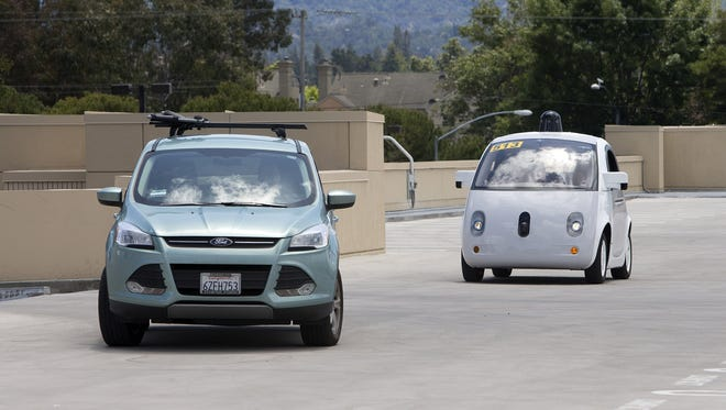 A two-seater prototype of Google's self-driving car, left, slows down as a Ford Escape crosses its path during a demonstration at Google on May 13, 2015 in Mountain View, Calif.
