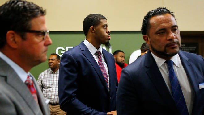 Former University of Memphis basketball player and Memphis Grizzlies hopeful D.J. Stephens (center) stands with his attorneys Murray Wells (left) and Arthur Horne following an appearance Friday in General Session Court Division 10 for arraignment on a domestic violence arrest.