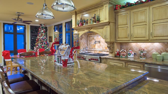 A large granite topped island with a ginger bread house leads into the breakfast area which has it's own colorful Christmas Tree