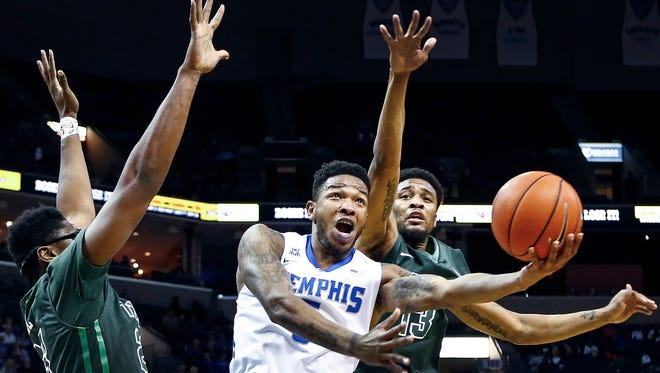 University of Memphis guard Markel Crawford (middle) drives to the basket against Tulane University defenders Blake Paul (left) and Malik Morgan (right) during first-half action at the FedExForum.
