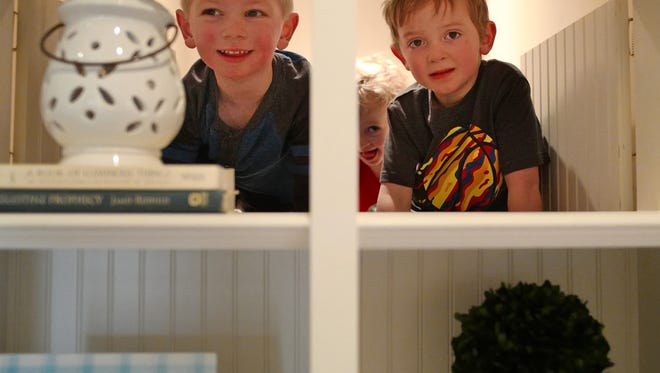 Neighbor Elliott Buzdiak, 3, plays with Leo Kuhl, 6, and his sister Charlie, 3 and peek from behind cupboards that have swing doors. (Richard Tsong-Taatarii/Minneapolis Star Tribune/TNS)