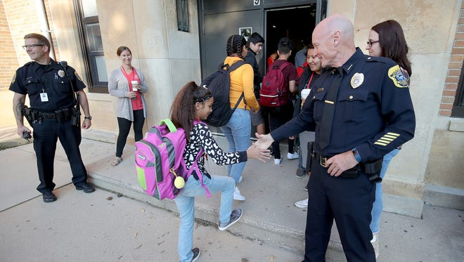 Green Bay Police Chief Andrew Smith greets students Tuesday on the first day of the fall semester at Washington Middle School in Green Bay.