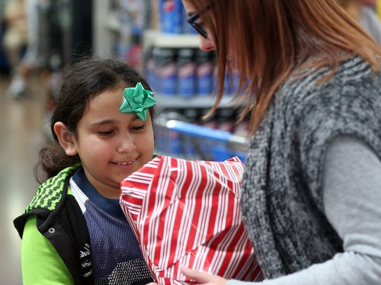 Lucy and Holly load Christmas presents as they are being wrapped after shopping during Operation Blue Santa on Saturday morning.