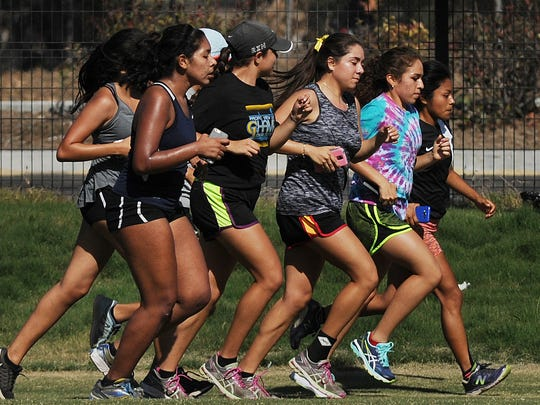 Members of the Channel Islands High girls cross country team practice at Oxnard College Park. The Raiders are aiming for their second straight league title.