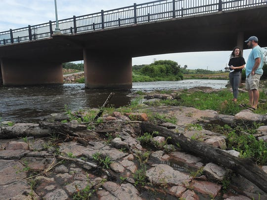 Hattie Johnson, a landscape designer at RiverRestoration.org, looks at the Big Sioux River in Falls Park with Mitchell Joldersma while talking about the feasibility of a whitewater river bed on Tuesday, July 28, 2015.