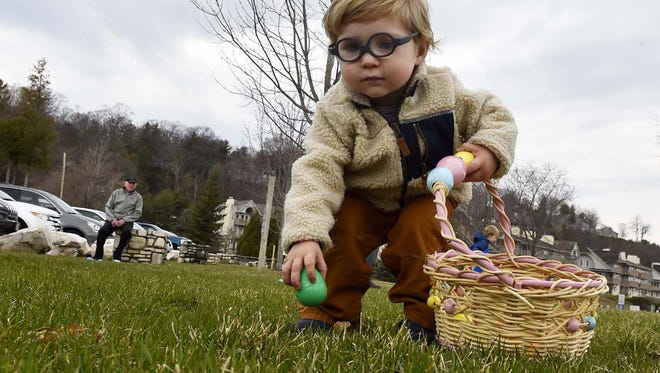 Liam Hockers of Milwaukee collects Easter eggs during last year's hunt at Waterfront Park in Sister Bay.