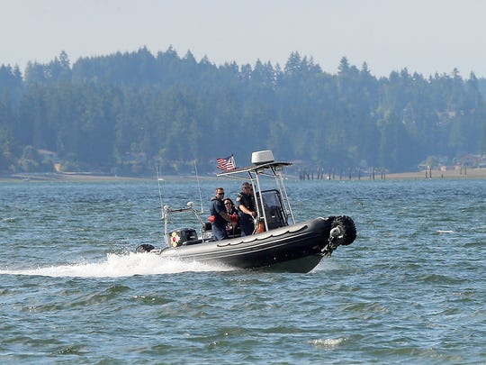CKFR's Jeff Wildes, Lt. Ryan Madison. Steve Whitish and  Ileana LiMarzi ride aboard Boat 51 as they head to the shore of Silverdale Waterfront Park on Thursday, July 20, 2017.