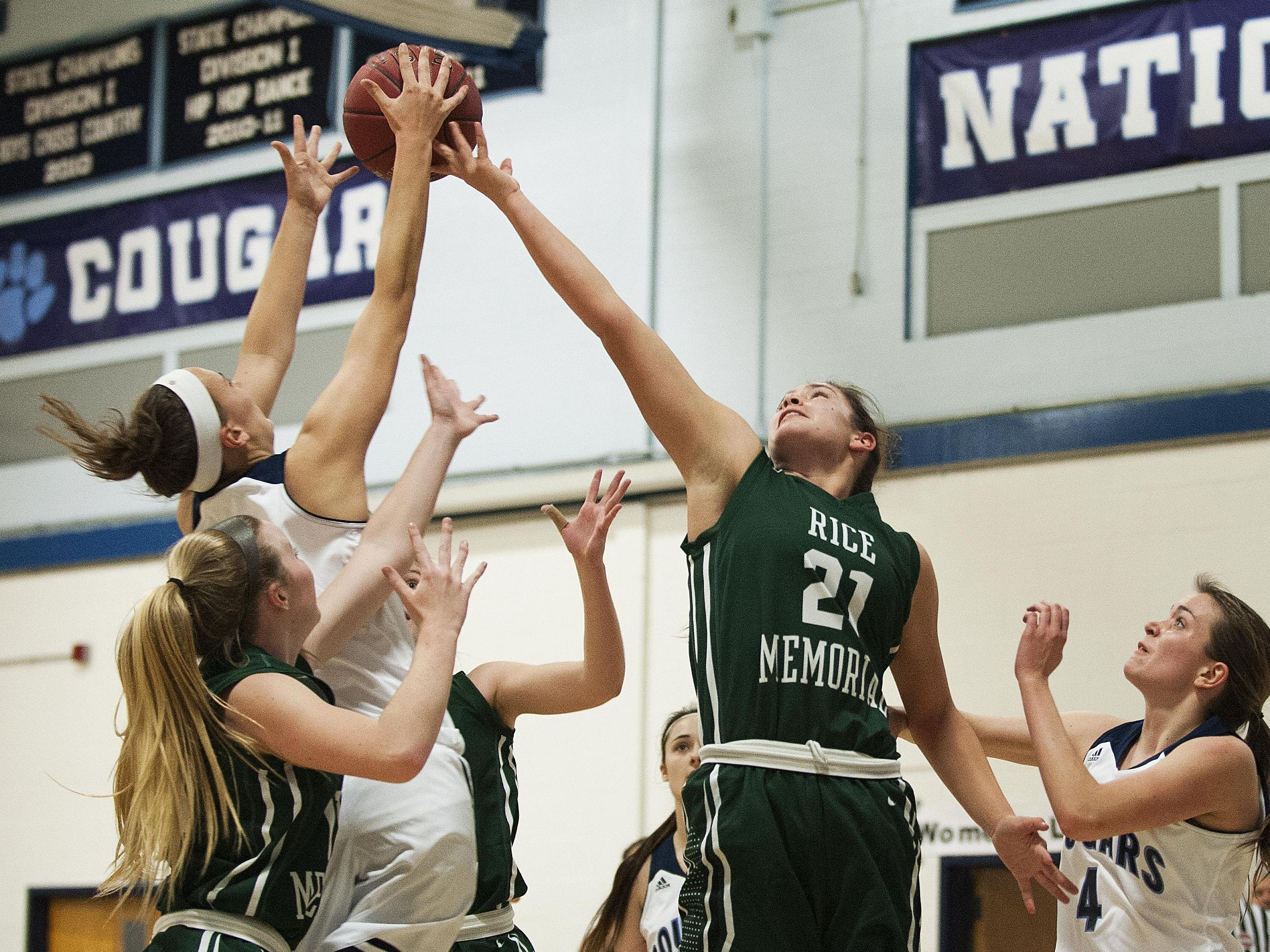 Rice forward Rachel Chicoine (21) and Mount Mansfield forward Katie Estes (14) battle for the rebound during the girls basketball game between the Green Knights and the Cougars on Friday night in Jericho.