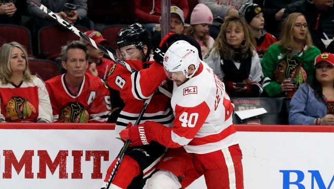 Blackhawks center Nick Schmaltz and Red Wings center Henrik Zetterberg battle for the puck during the second period Sunday in Chicago.