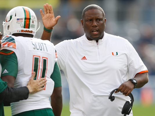 FILE - In this Nov. 27, 2015, file photo, Miami head coach Larry Scott congratulates Miami wide receiver Rashawn Scott (11) after the team scored a touchdown in the first quarter of an NCAA college football game against Pittsburgh, in Pittsburgh. Scott, named as offensive coordinator at Tennessee in January, has a tough task taking over an offense lacking experienced players. But he's faced bigger challenges than this. The Volunteers believe Scott's passion for the game and the experience he got as Miami's interim head coach in 2015 make him an ideal fit for this kind of assignment. (AP Photo/Keith Srakocic, File)