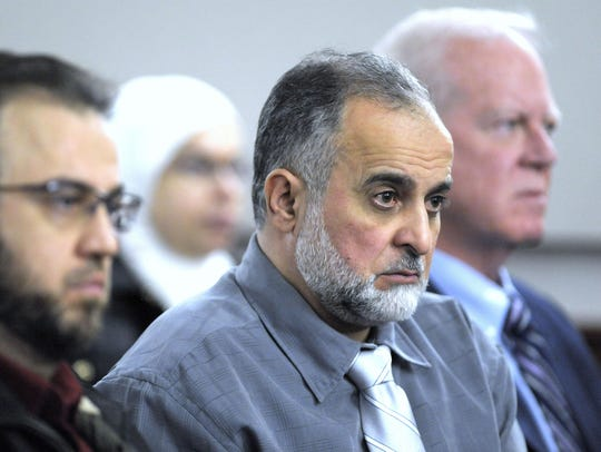 The defendant's father, Basel Altantawi, center, listens