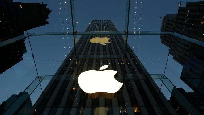 The Apple logo is illuminated in the entrance to the Fifth Avenue Apple store, in New York.