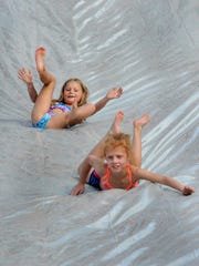 People go down the water slide at First Baptist Church
