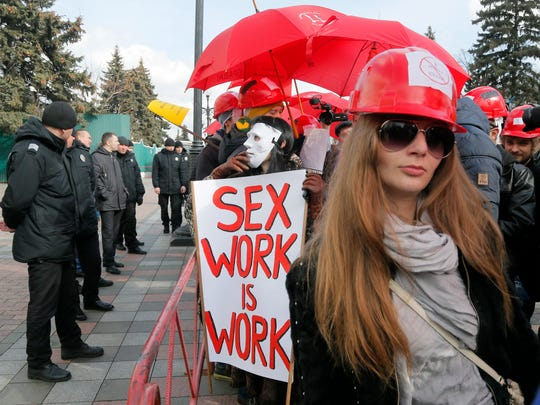 A sex worker holds a banner reading 'Sex work is work' in front of Cabinet of Ministers in Kiev, Ukraine.