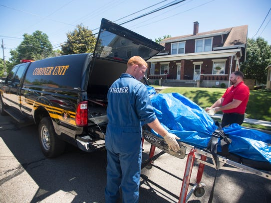 The Hamilton County coroner's office removes the body of a 66-year-old white male from a third floor apartment in Norwood. Justin Weber, death investigator, right, said the suspected cause was an overdose.