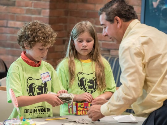 Xander Yoder and Kya Phillips learn count money at a young entrepreneurs event at Kellogg Community College on Wednesday.
