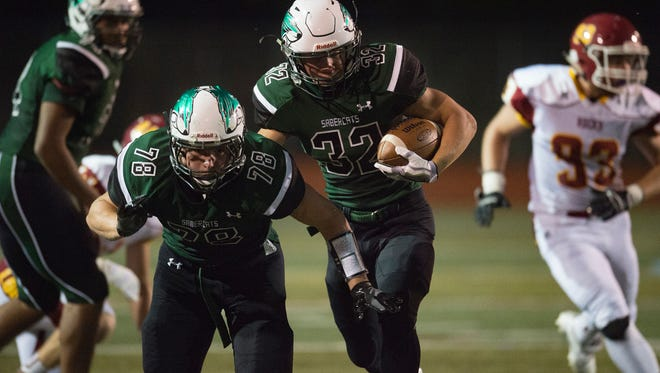 Fossil Ridge running back Casey Knutsen carries the ball in a game last season. Knutsen will play both defense and offense for the SaberCats.