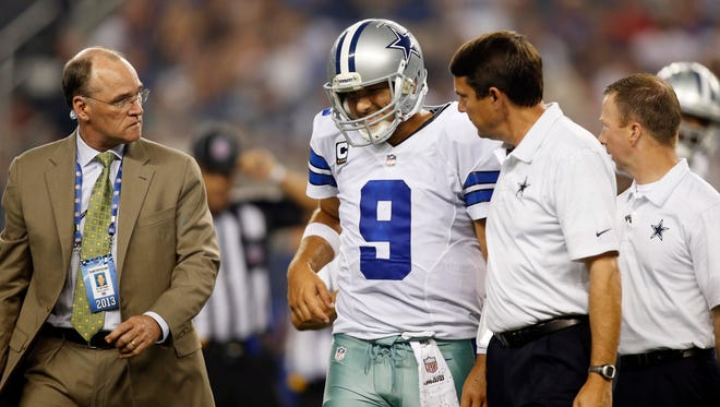 Dallas Cowboys quarterback Tony Romo (9) is escorted off the field with team physician Dan Cooper and training personnel in the second quarter of the game against the New York Giants at AT&T Stadium.