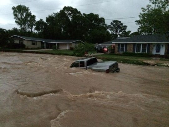 High water from torrential rains sweeps away a vehicle in the Cordova Park area of Pensacola, Fla., on April 30, 2014.