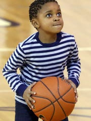 D'Vonne Johnspn, 7, of Newark, lines up a shot during the Hoops for Hunger event at Newark High School hosted by the boys basketball team and the Fellowship of Christian Athletes Saturday.