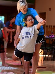 Imaginarium Camp coordinator helps Karcyn Williams with a yoga pose during camp, Tuesday, June 26.