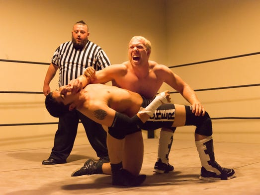 """Robert """"Chico Adams"""" Adams grabs Blake Archer by the face and leg."""