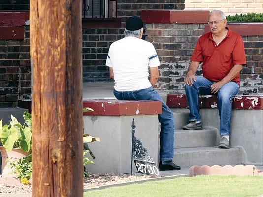 Residents in the Manhattan Heights neighborhood visit on the front steps of their home, where a new power line pole has been placed. The poles are part of an El Paso Electric Company project.