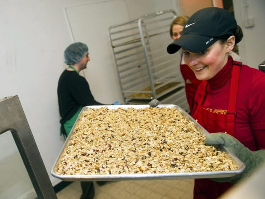 Sarah Lanphier, seen here loading a tray of granola into the oven, opened Nuts About Granola with her mother Gayle Lanphier in 2008. The company is moving its offices and production of its branded products to a building on West Philadelphia Street near its retail store.