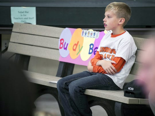 Christian Bucks, a second-grader at Roundtown Elementary School in Manchester Township, sits on his 'buddy bench.' When children feel left out or need a friend, they can sit on the buddy bench. Then other children will approach the students on the bench and ask them to talk or play.