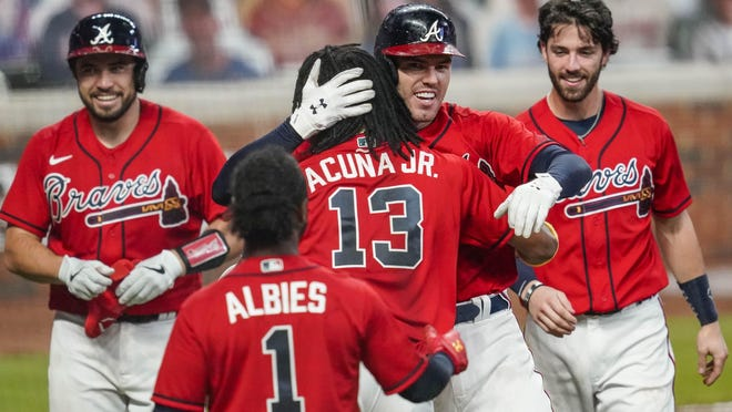 Atlanta Braves first baseman Freddie Freeman (5) reacts with center fielder Ronald Acuna Jr. (13) after hitting a game winning two run home run against the Boston Red Sox at Truist Park.